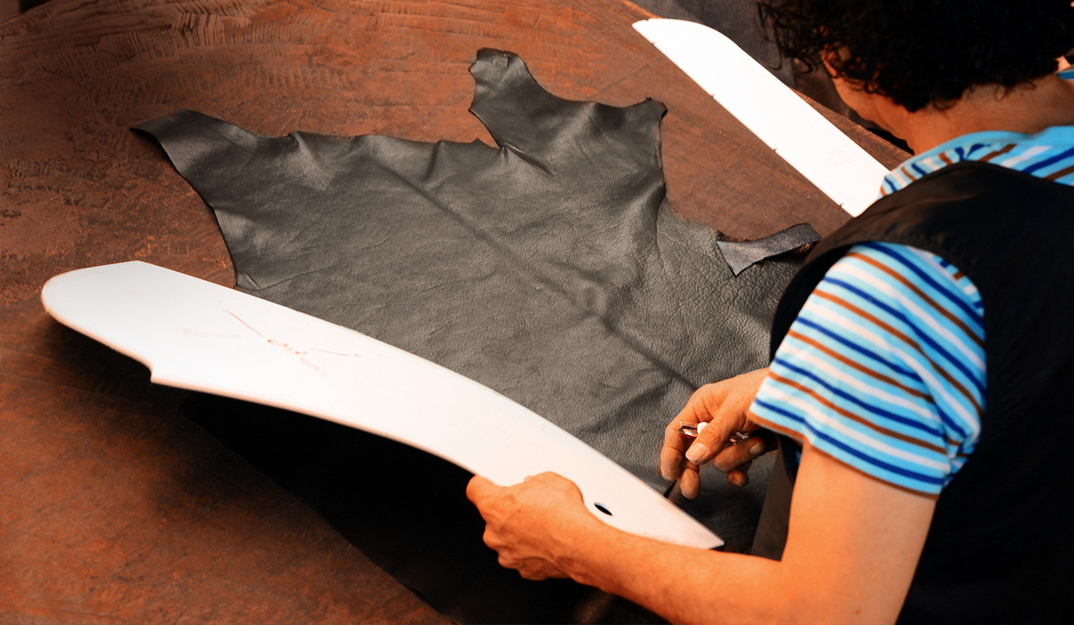 Woman is cutting leather using a pattern